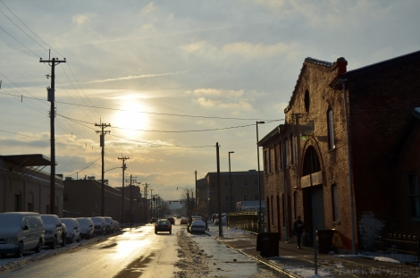 The sun sets over a  Newport, KY street.