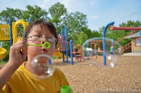 A young boy blows bubbles at a KY Park.